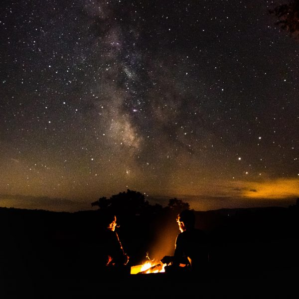 Two people sitting by campfire with Milky Way above